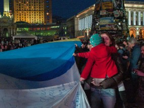 Young woman with her daughter hold the flags of Ukraine and Crimea stitched together