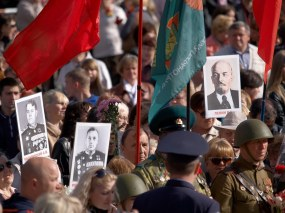 People at parade hold portraits of Lenin and soviet generals
