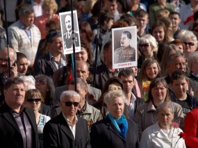 People at parade hold portraits of Stalin and soviet generals