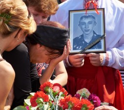 The mother of the died soldier crying on the coffin