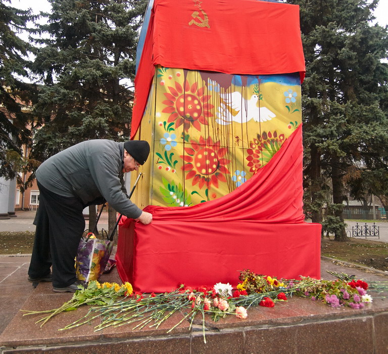 A man taking off flags from the former Lenin's monument