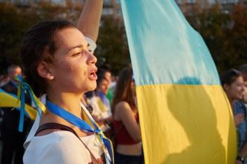 Girl with Ukrainian flag singing the anthem