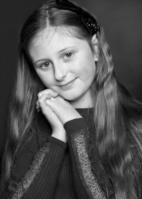 black and white portrait of girl with bow in hair