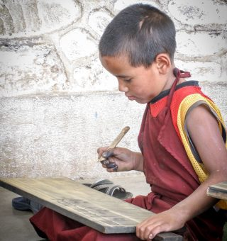 Young monk learning to write Tibetan script