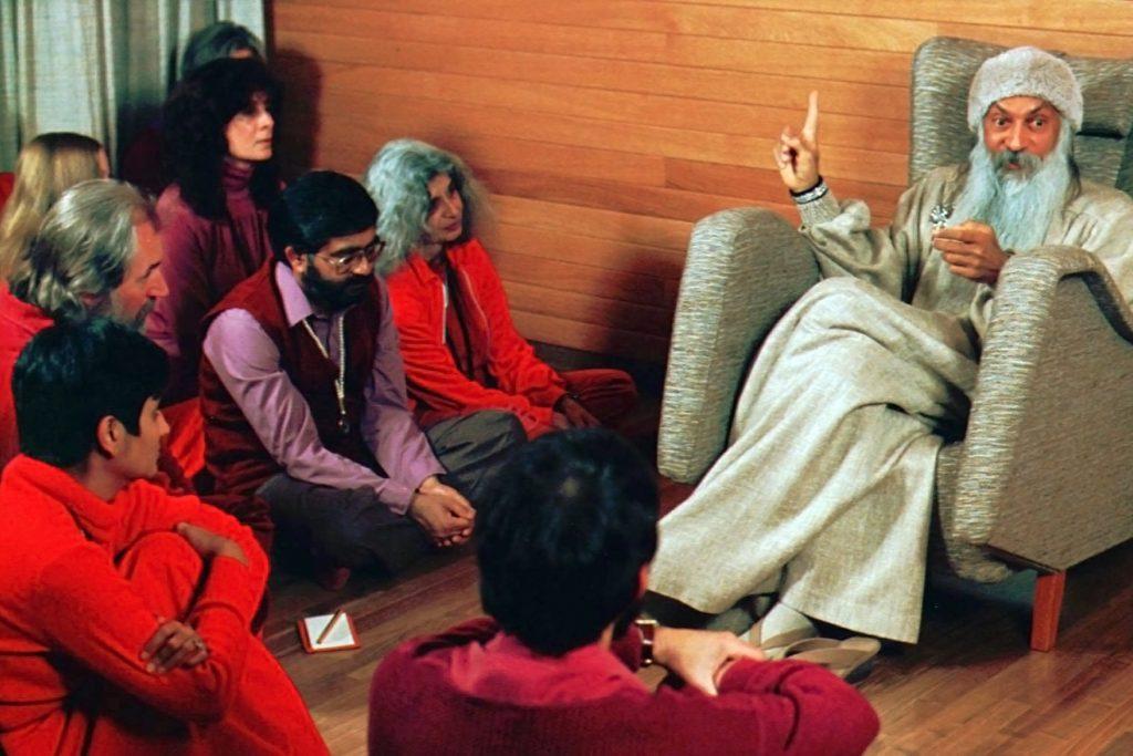 Rajneesh cult followers seated around Osho