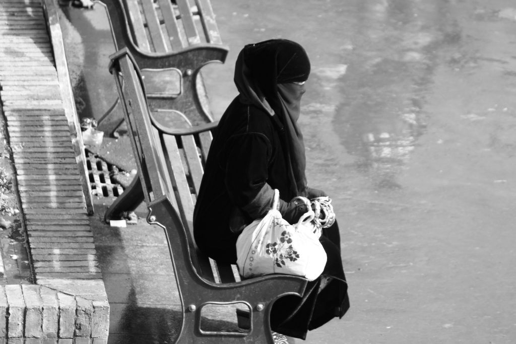 woman in Niqab sitting on bench