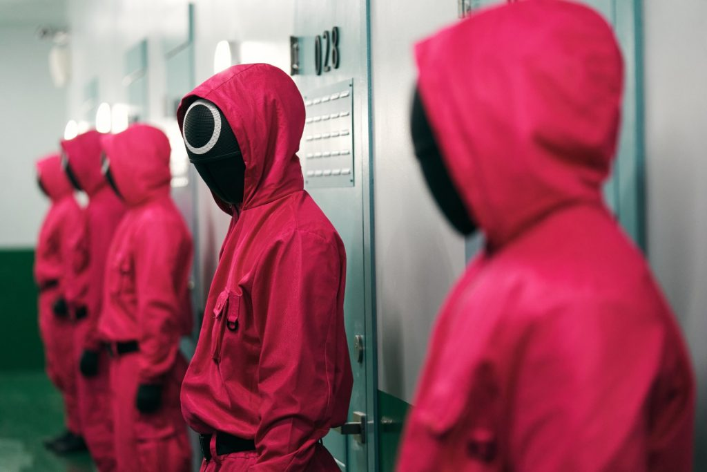 masked people in pink jumpsuits
