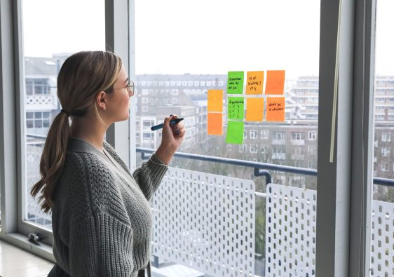 Woman in Gray Sweater Holding pen writing on post it notes on window