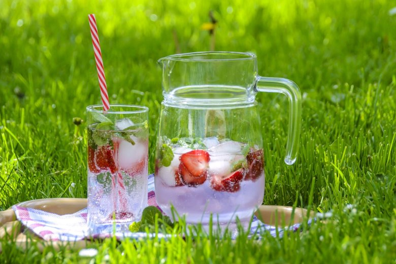 Jug and glass of strawberry water on the grass