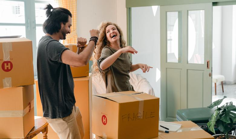 Happy couple dancing while packing boxes