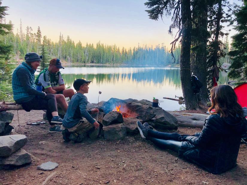 A family siting around a campfire by the lake