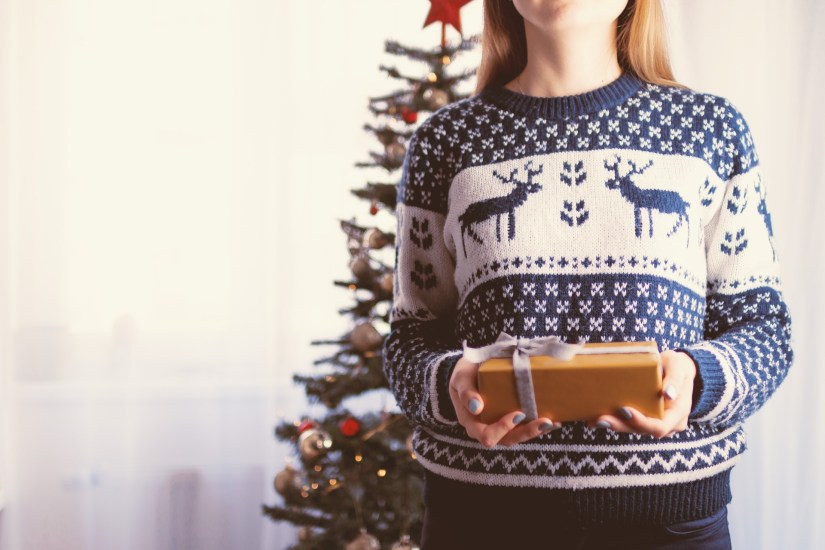 Woman in christmas jumper holding gift