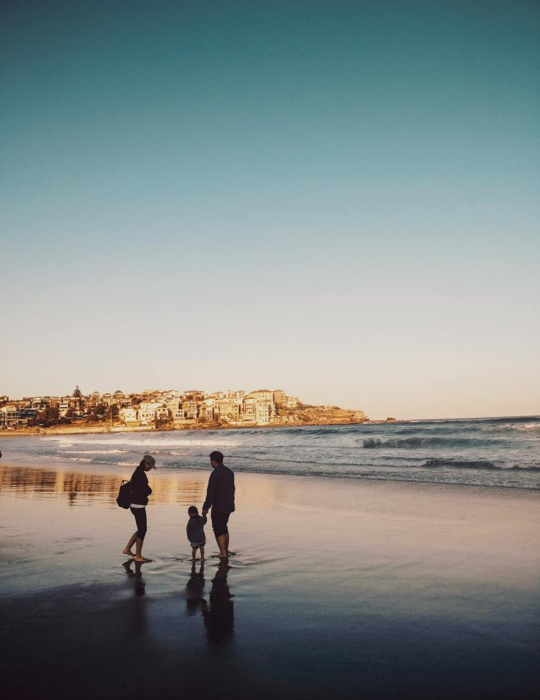 Man and Woman Walking With Boy in Seashore