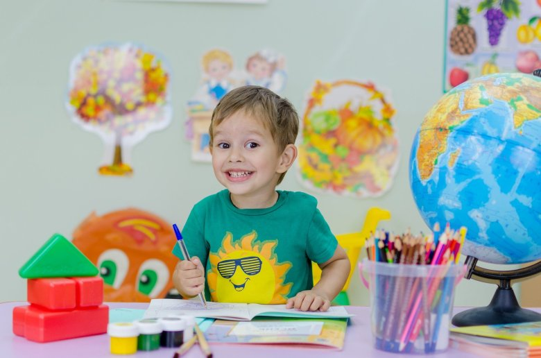 A smiling child sitting at a table with colourful pencils.