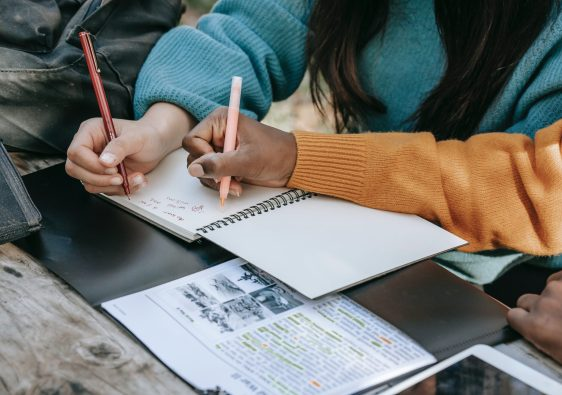 Crop unrecognizable diverse schoolgirls taking notes in copybook in park