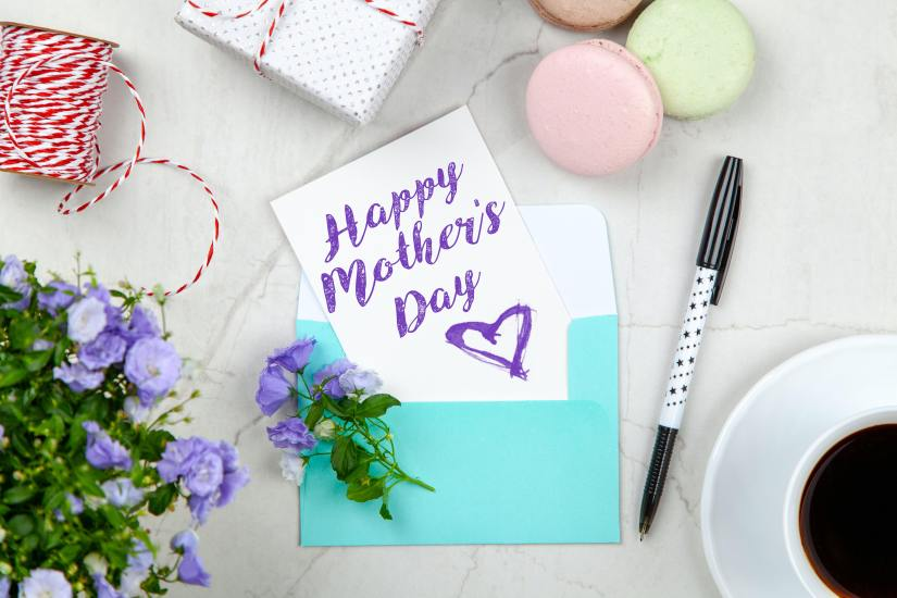 Happy Mothers Day Card Beside Pen, Macaroons, Flowers, and Box Near Coffee Cup With Saucer
