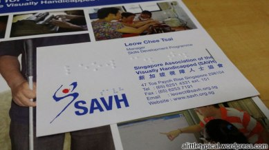 A brochure on SAVH and a special name card with braille letters.