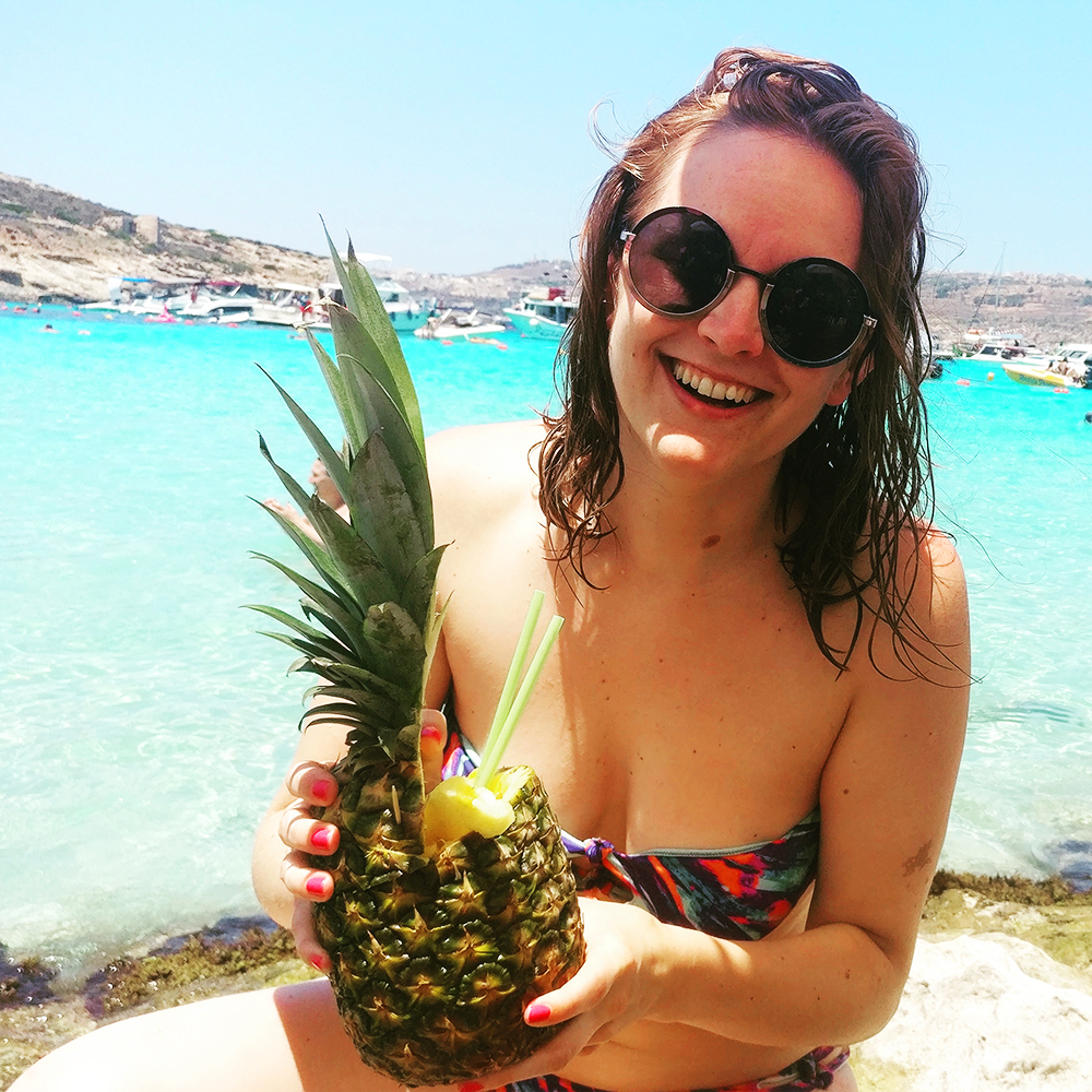 Drink a cocktail from a pineapple at Blue Lagoon, Comino - Best beaches in Malta | Aliz's Wonderland