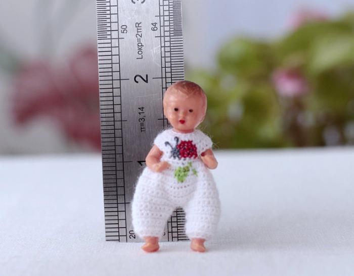 На фото: куколка, ростом 2 дюйма, одета в вязаный комбинезончик от Creativhook