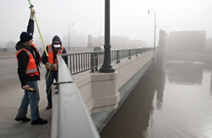 Checking the water level on a bridge between Fargo and Moorhead. Photo from Minnesota Public Radio.