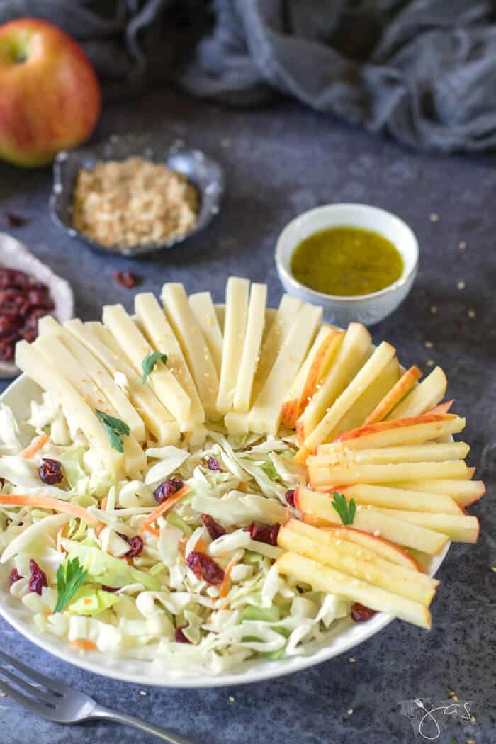 Shredded cabbage mixed with apples, cheese, raisins, and sesame seeds is super delicious and quick to make.