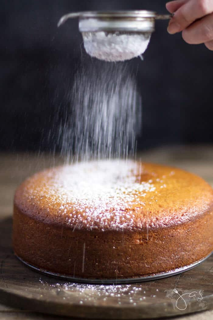 dusting sugar over French lemon yogurt cake
