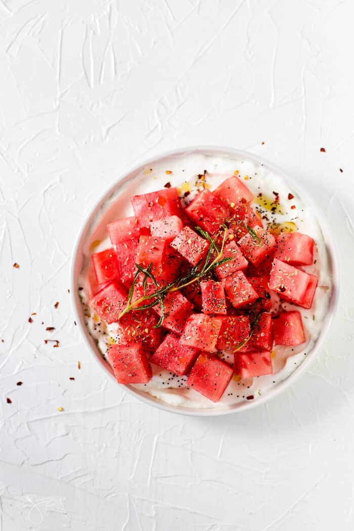 This refreshing Israeli Watermelon Yogurt Summer Salad with rosemary, crushed pepper flakes, poppy seeds, and mintis a little sweet, a little savory, little tart, and a whole lot delicious.   allthatsjas.com   #summer #salad #glutenfree #vegetarian #easy #fast #recipes #reicpeofthemonth #healthy #nutritios #potlucks #party #holidays
