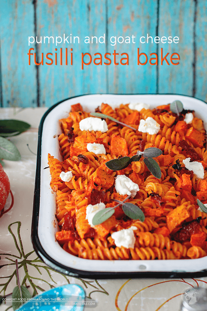 Ready for a different fall-inspired pumpkin recipe? You will love this easy pumpkin and goat cheese fusilli pasta bake. In combination with sage and sun-dried tomatoes, it yields a flavorful and ultimate grown-up pasta casserole.   allthatsjas.com   #pastabake #oven #vegetarian #pumpkin #goatcheese #casserole #comfortfood #worldfood #autumn #fall #noodleswithoutborders #recipes #holidaymeal #thanksgiving #allthatsjas