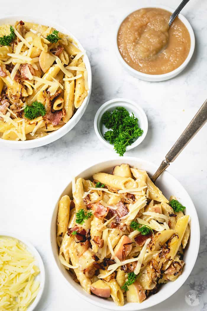 Two bowls of mac and cheese recipe from Switzerland with a serving of applesauce.