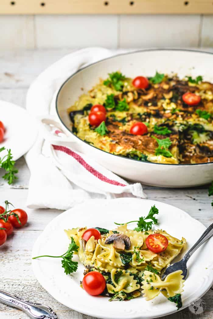 A white skillet and a plate with pasta frittata Spanish stovetop dish.