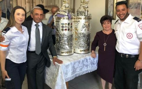 """שנתיים לאחר שמנשה כהן לקה בדום לב הוא תרם ספר תורה לבית הכנסת ואורחי הכבוד של מנשה היו החובשים והפראמדיקים של מד""""א שהצילו את חייו"""