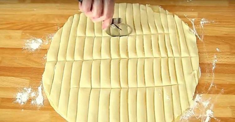Απλώνει φύλλα για πίτα και τα κόβει σε λωρίδες.