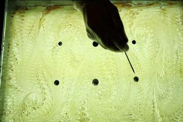 Ρίχνει 6 σταγόνες σε μία επιφάνεια με νερό