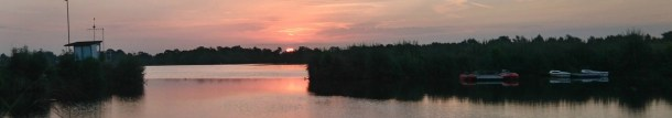 Dawn breaks over a large Middlesex stillwater in summer.