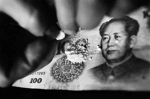A drug user brakes up heroin on a new 100 yuan note. A new bill is used so that none of the drug gets caught in wrinkles or folds.