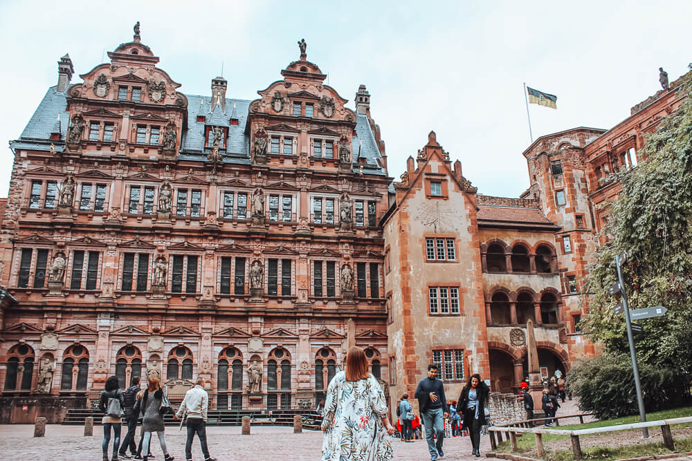 Woman looking up at the ornate Heidelberg castle a wonderful thing to do in Heidelberg city
