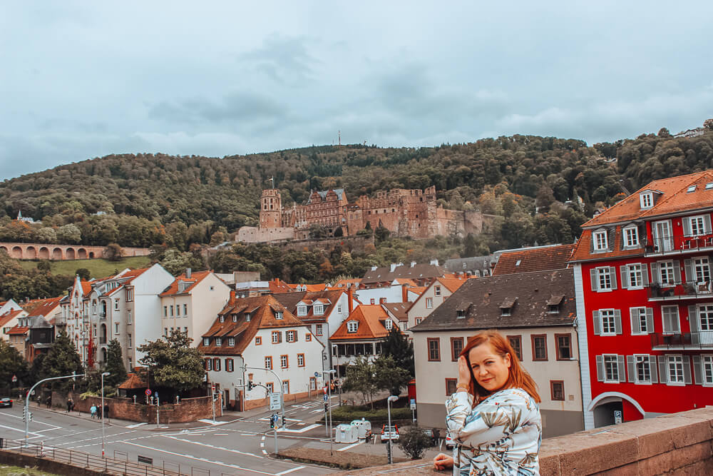 Woman standing on the alte brucke in Heidelberg Germany the perfect way to spend one day in Heidelberg Germany