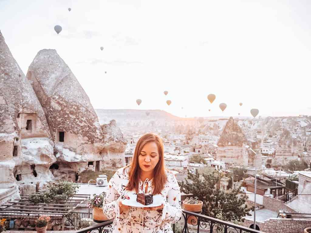 Woman blowing out candles on her birthday cake in Cappadocia Turkey