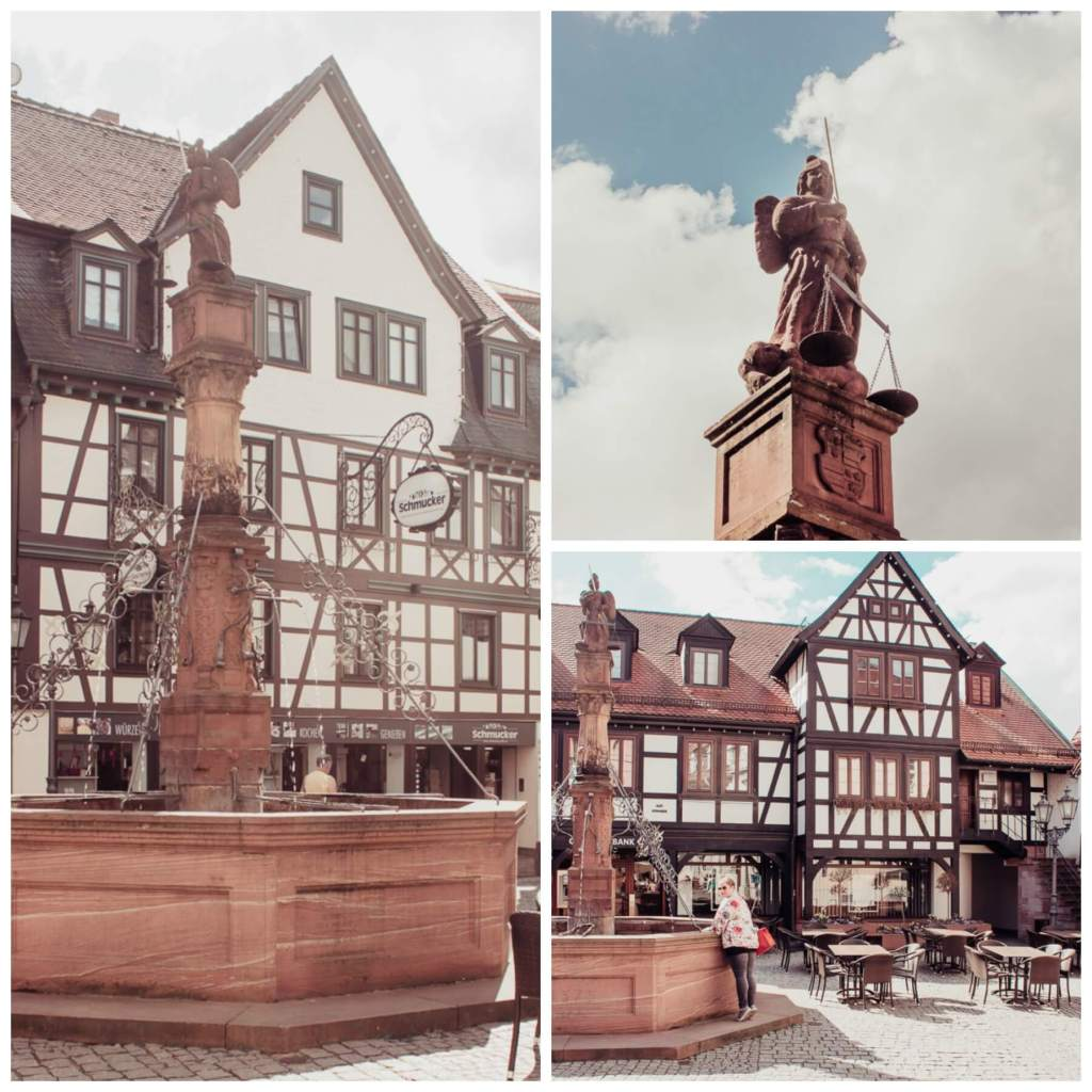 The fairytale village of Michelstadt Germany with an ornate fountain, marktbrunnen, in the town square and statue of the archangel Michael