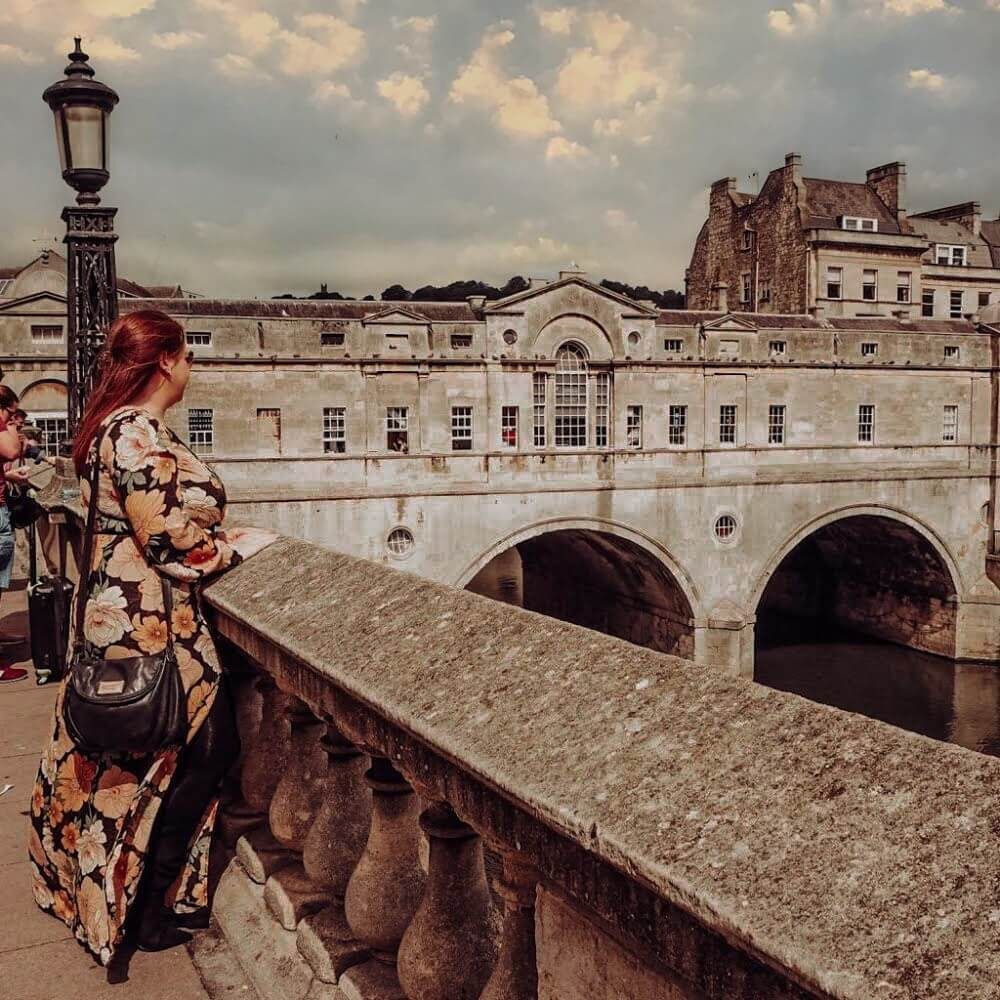 Woman in a floral dress looking over the Pulteney Bridge in Bath UK