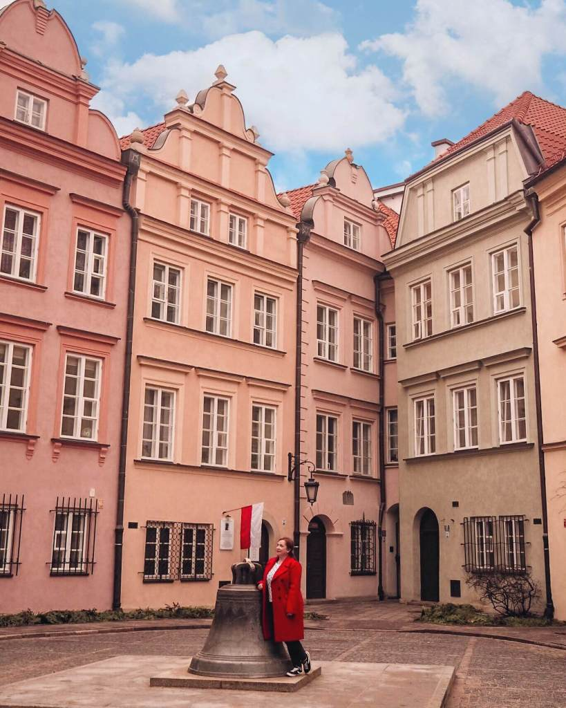 Woman in a red coat looking up at the pastel buildings in Warsaw's alleyways. A pretty Instagram spot in Warsaw