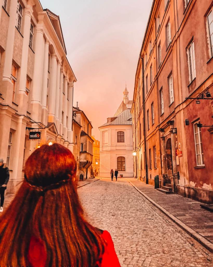 Woman with red hair looking down the cobbled streets of Warsaw at dusk