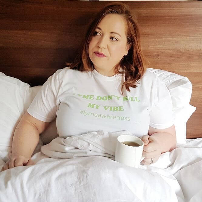A woman with Lyme Disease lying in bed and drinking a herbal tea