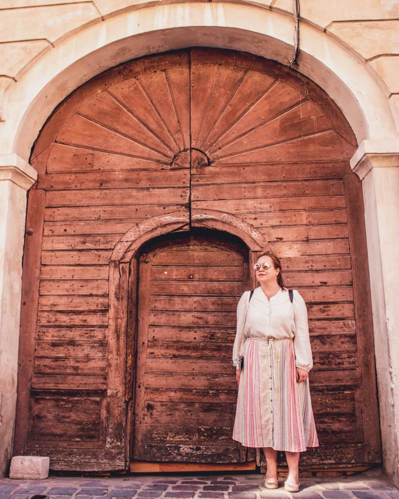 Woman standing in front of a brown doorway in Brasov Transylvania Romania