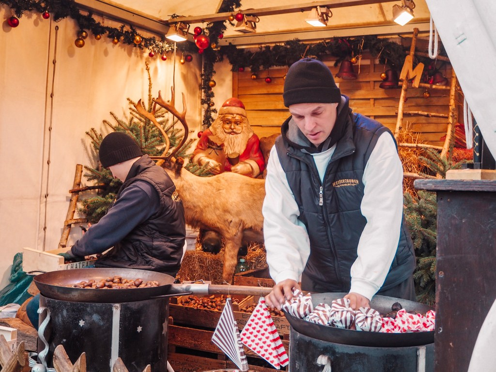 Two men roasting chestnuts at Hamburg Christmas market
