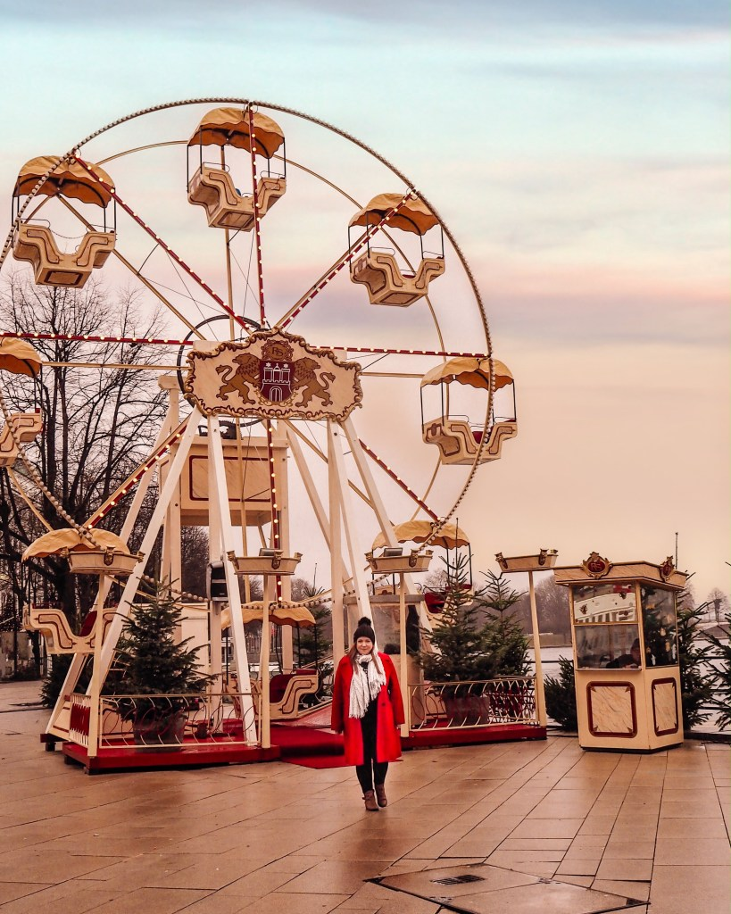 Girl in red coat standing in front of a ferris wheel at White magic by the Jungfernstieg Hamburg Christmas markets