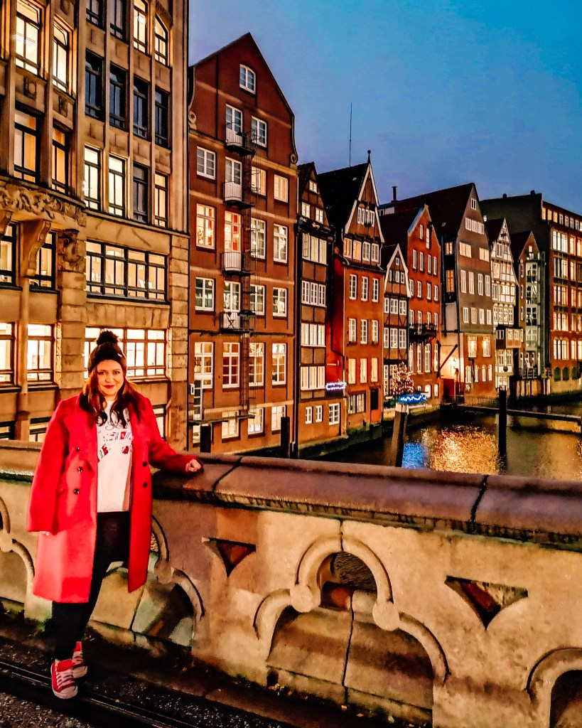 girl in red coat standing on at bridge at Deichstraße Hamburg Germany