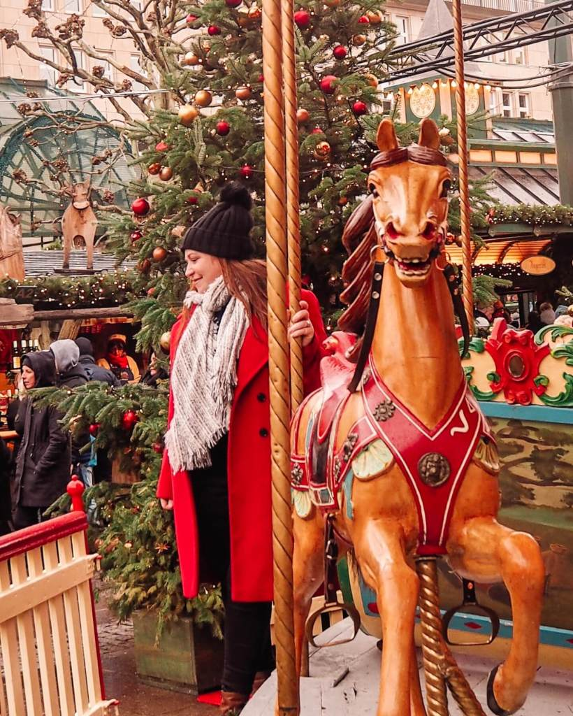 Girl in red coat and black hat on a carousel at Hamburg Christmas Markets