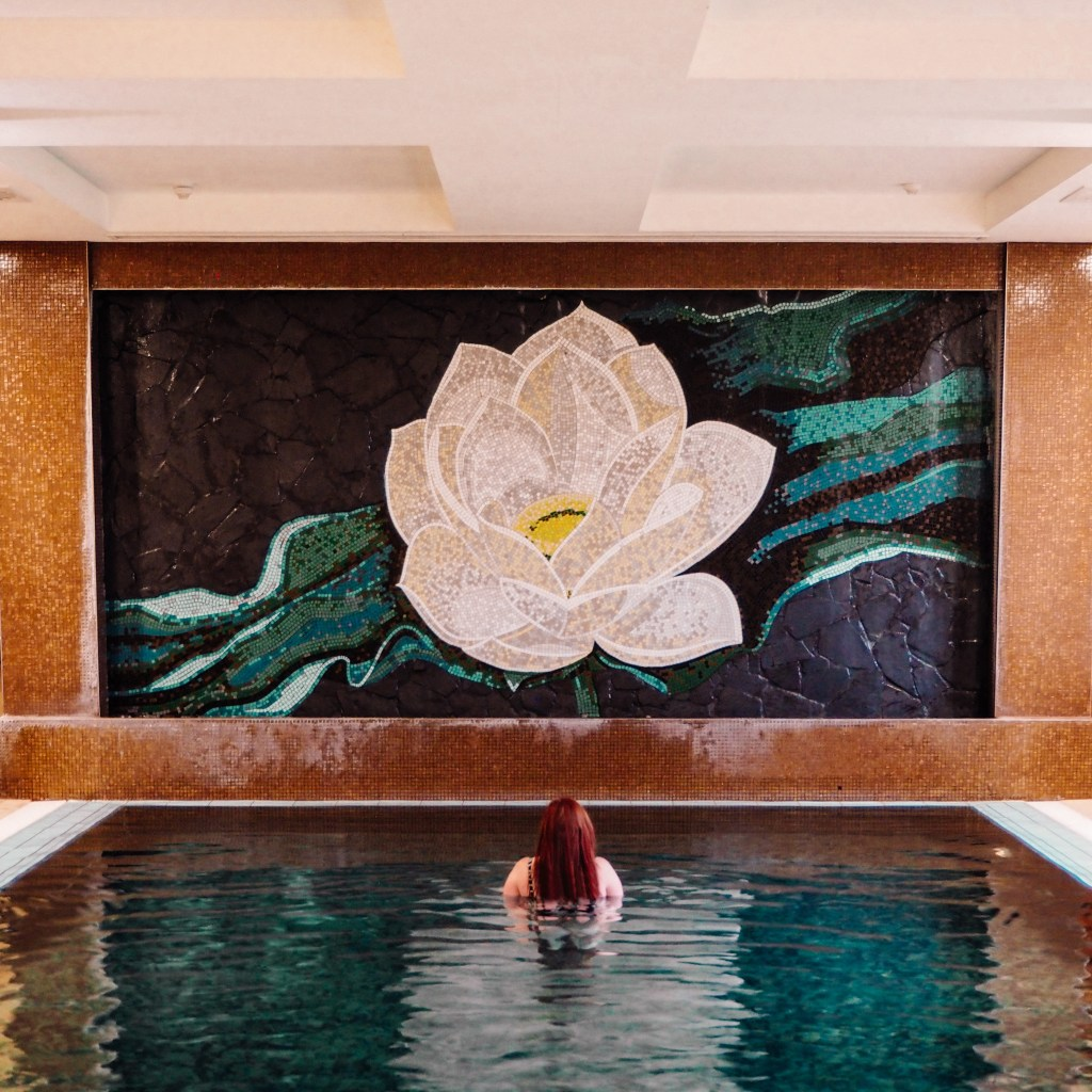 Travel blogger All about RosaLilla in the infinity pool at the Thai spa in Lough Erne. There is a large flower mural on the wall.