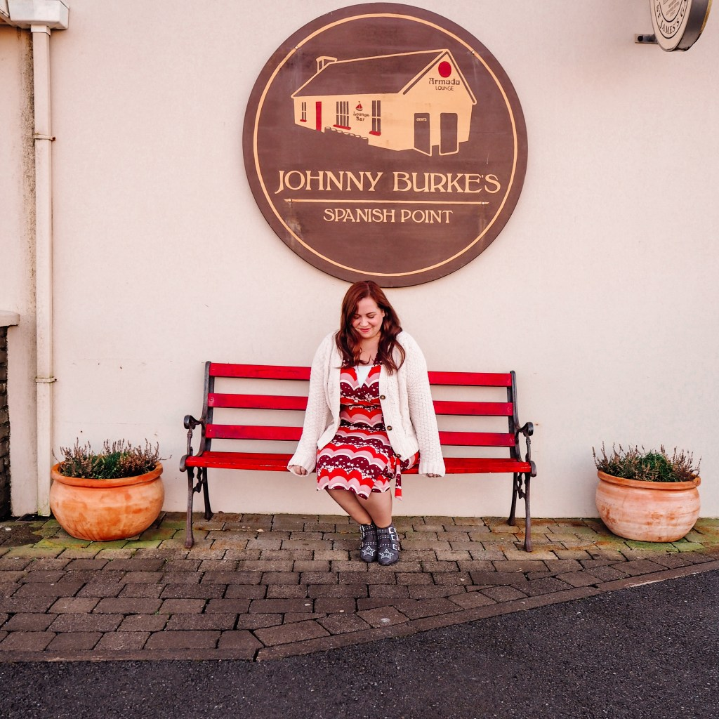 Woman sitting on a red bench outside Johnny Burke's Pub in County Clare Ireland